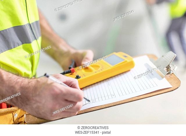 Close-up of electrician taking notes