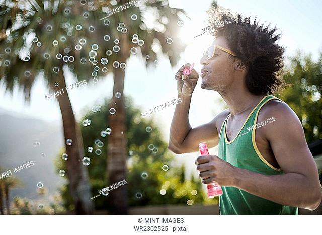 A young man blowing bubbles using a bubble wand
