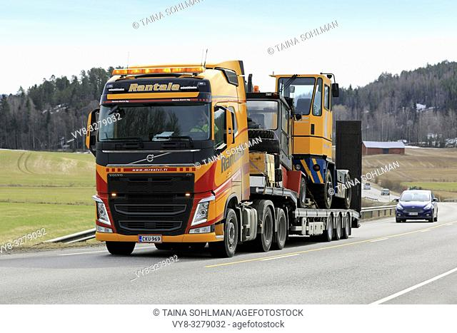 Salo, Finland - March 29, 2019: Yellow Volvo FH truck of Rantala Yhtiot pulls Kalmar terminal tractor on Noteboom trailer along highway in the spring