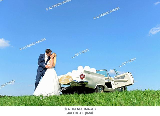 Bride And Groom Next To Open Top Classic Car On Wedding Day