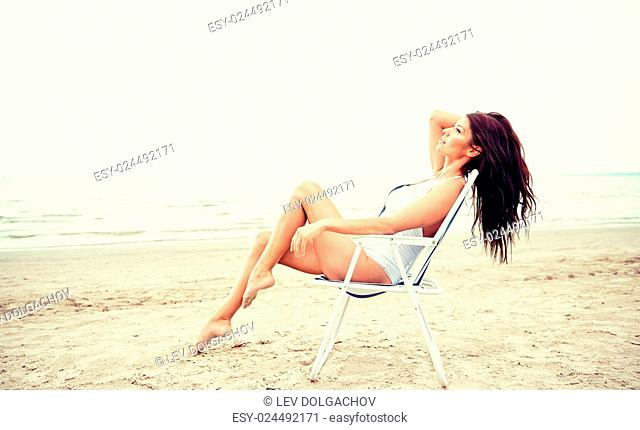 summer vacation, tourism, travel, holidays and people concept - happy young woman sunbathing in lounge or folding chair on beach