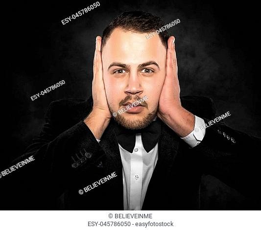 Man in suit covering his ears over dark background