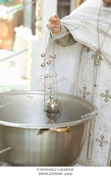 Priest holding chalice in bowl