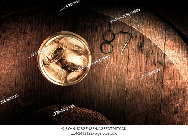 Top down view on a glass of vintage scotch whisky on wooden tabletop background with copyspace. Glass of 87