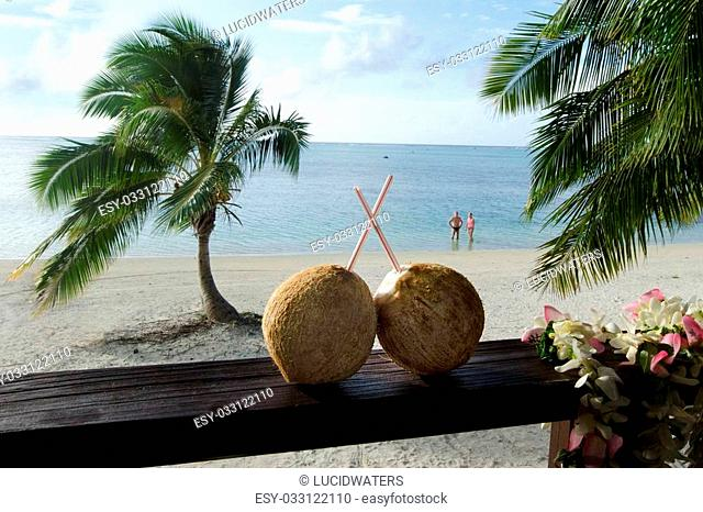 Two coconuts with straws on bungalow balcony with couple of tourist on honeymoon vacation in the background