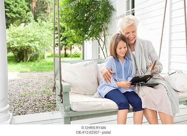 Woman and granddaughter reading on porch swing