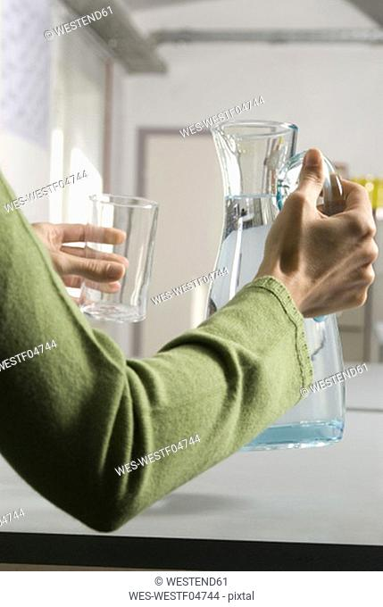 Woman pouring water, close-up