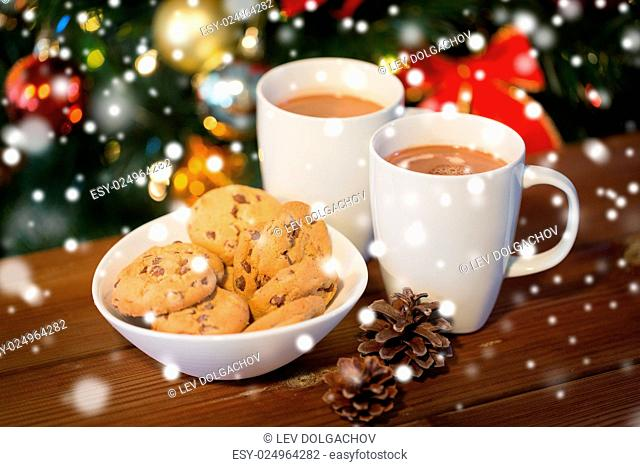 holidays, winter, food and drinks concept - close up of oatmeal cookies, cups with hot chocolate or cocoa drink and pinecones on wooden table over christmas...