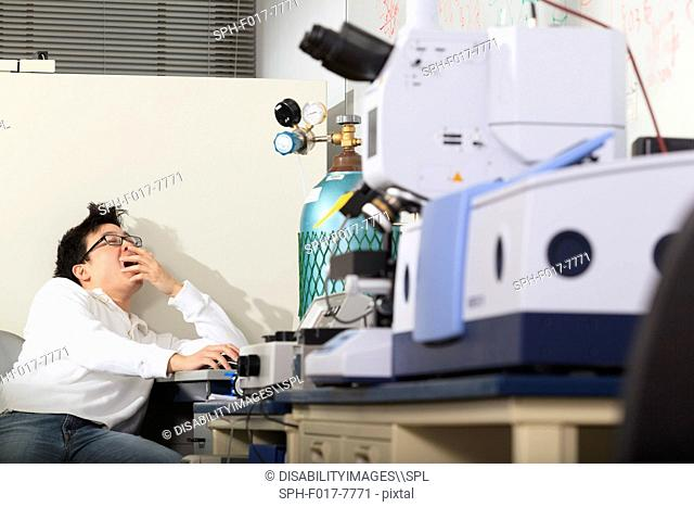 Engineering student using keyboard for chemical analysis instrument and yawning in a laboratory