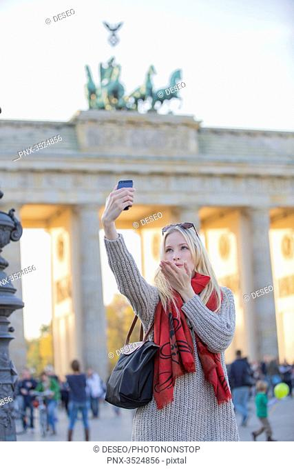 Pretty blonde woman doing a selfie and sending a kiss in front of the Brandenburg Gate in Berlin, Germany