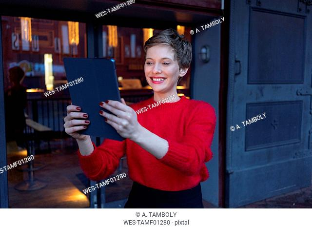 Portrait of smiling businesswoman taking selfie with digital tablet outdoors