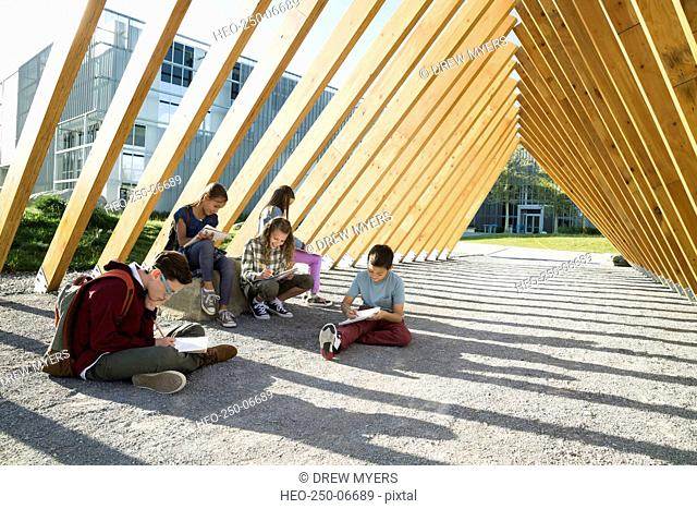 Students doing homework under wood beam walkway
