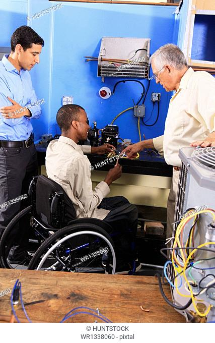 Instructor discussing condenser coil on refrigeration unit with student in wheelchair