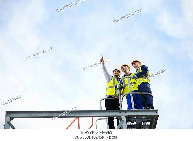 Workers overlooking construction site