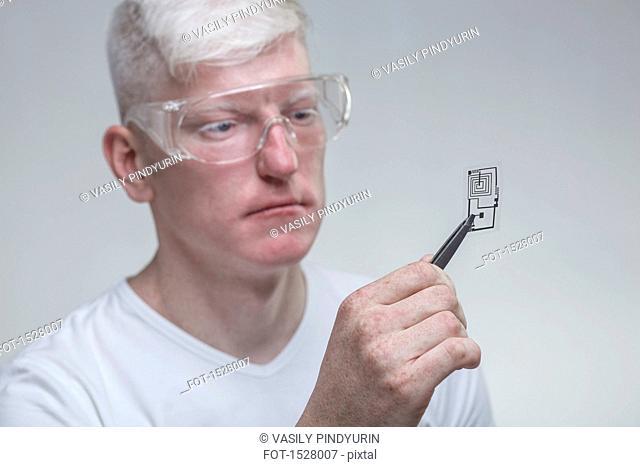 Albino man wearing protective eyewear while examining chip against gray background