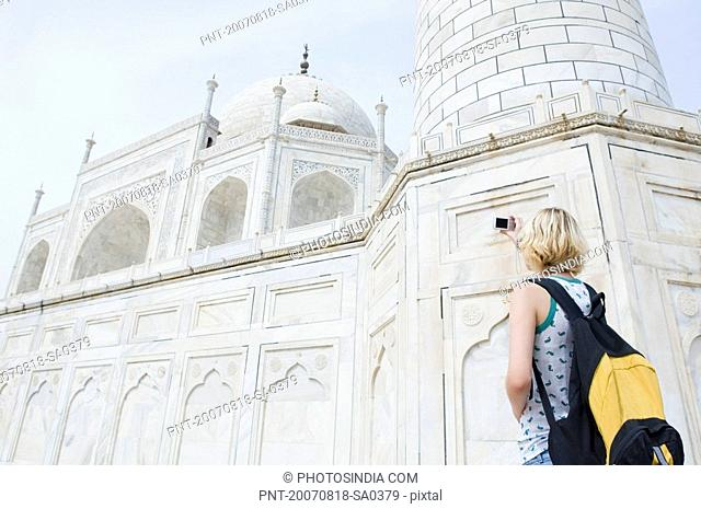 Rear view of a young woman taking a picture of a mausoleum, Taj Mahal, Agra, Uttar Pradesh, India