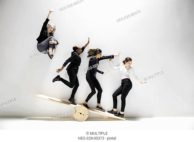Businesswoman jumping and sliding on seesaw against white background