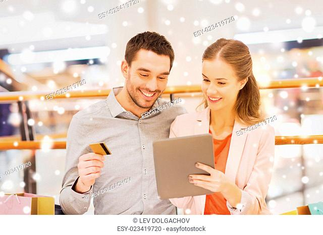 sale, consumerism, technology and people concept - happy young couple with shopping bags and credit card pointing finger to tablet pc computer in mall with snow...