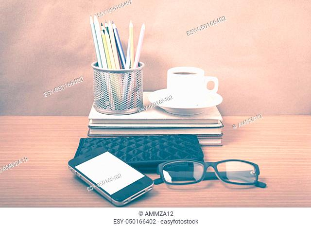 office desk: coffee with phone, stack of book, eyeglasses, wallet, color pencil box on wood background vintage style