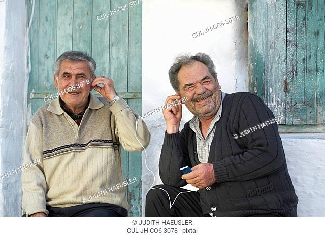 Two mature men sharing earphones and laughing