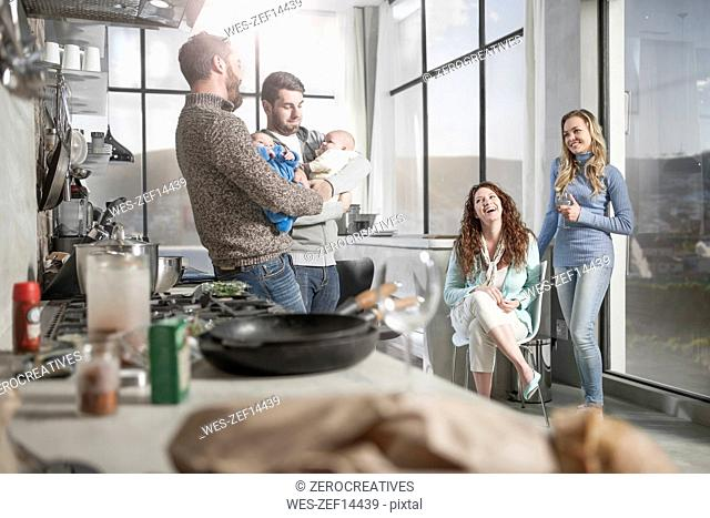 Two wives watching husbands holding their babies in kitchen