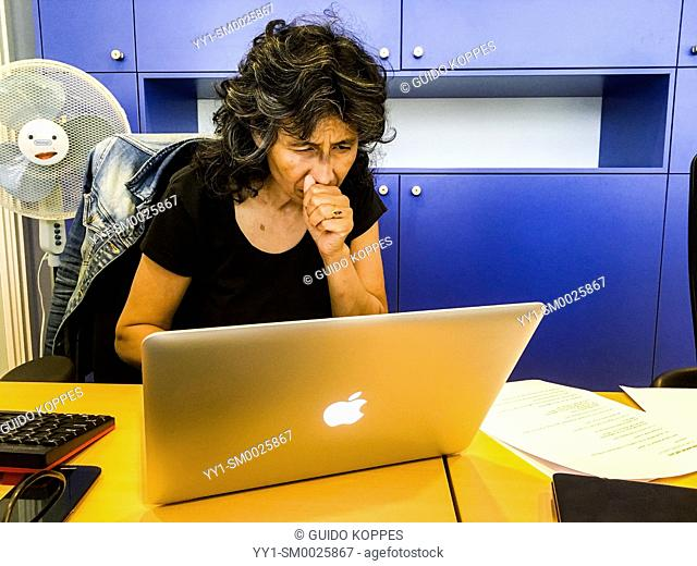 Tilburg, Netherlands. Female computer wizard hard at work installing printer drivers on a employee's Notebook computer