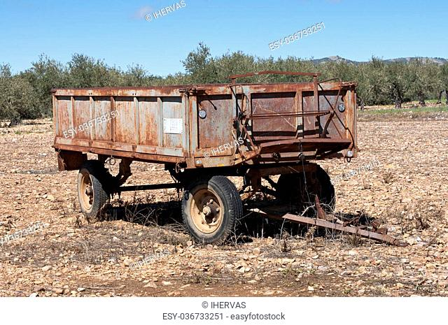 Old farm trailer on a fallow field. At the background an olive grove. Photo taken in La Fuencaliente, Ciudad Real Province, Spain