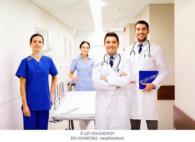 clinic, profession, people, health care and medicine concept - group of happy medics or doctors with gurney at hospital corridor