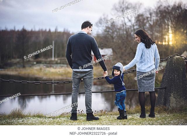 Small boy with parents during walk