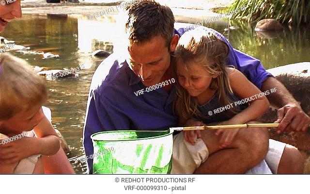 Family in Park, fishing in stream