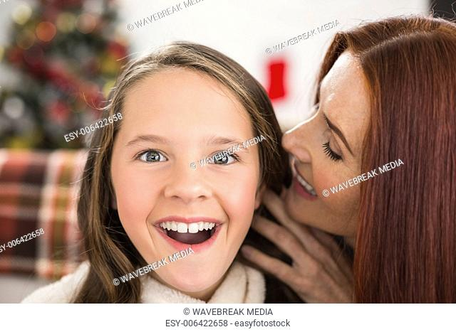 Mother telling her daughter a christmas secret