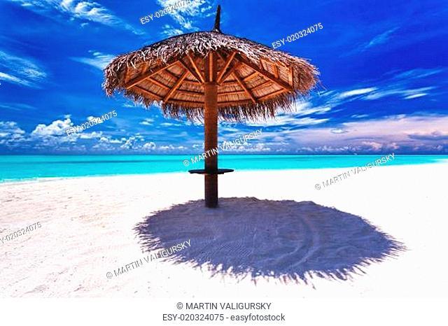 Beach umbrella on white sand next to lagoon