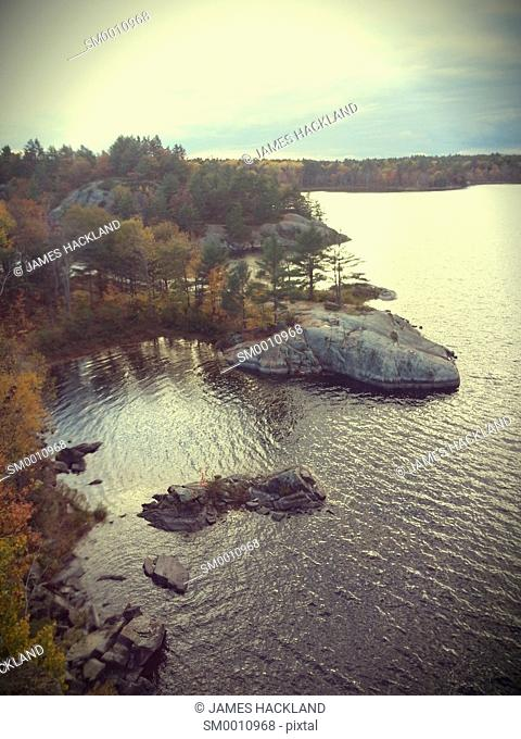 View from a cliff in autumn at sunset of McCrae Lake and it's shoreline. Muskoka, Ontario, Canada