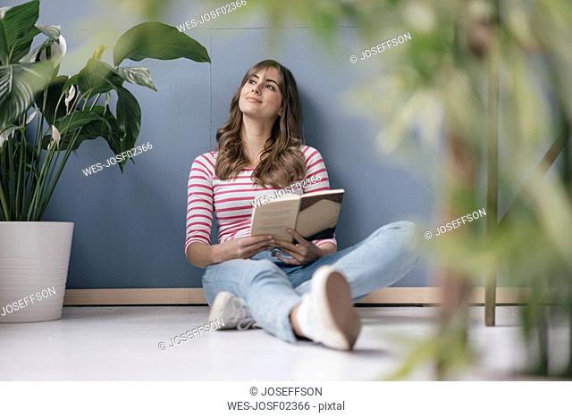 Woman sitting on ground in her new home, reading a book, surrounded by plants
