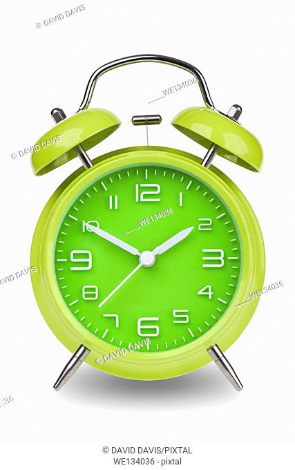 Green alarm clock with the hands at 10 and 2 isolated on a white background
