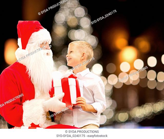 santa claus and happy boy with christmas gift