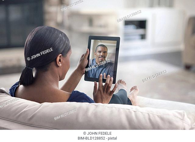 Woman video conferencing with father on digital tablet