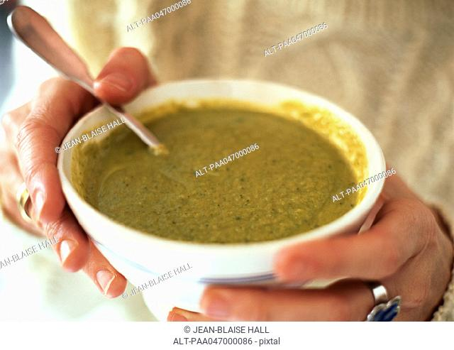 Hands holding bowl of leek soup, close-up
