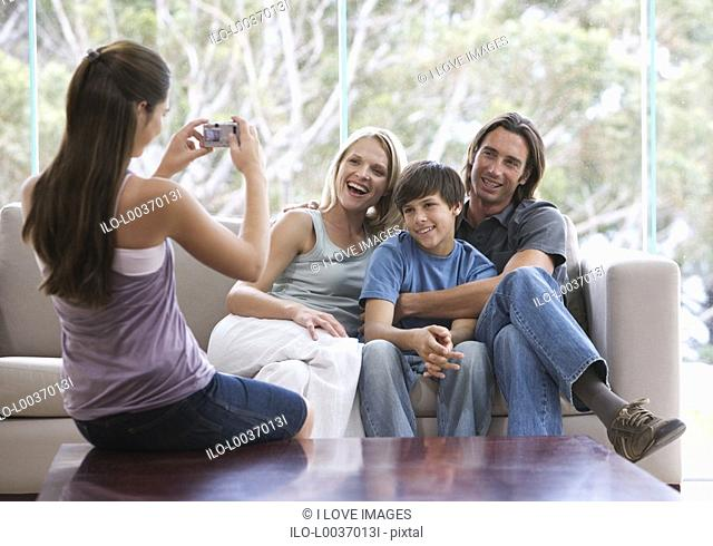 A young girl taking a photo of her family sitting on a sofa