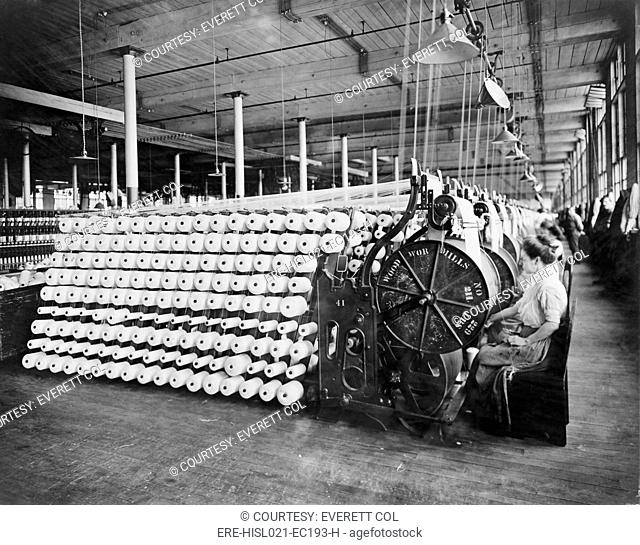 Women working at textile machines, beaming and inspecting yarn, at the American Woolen Company, Boston. The beaming process prepares the warp
