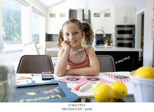 Portrait smiling girl making lemonade sign at dining table