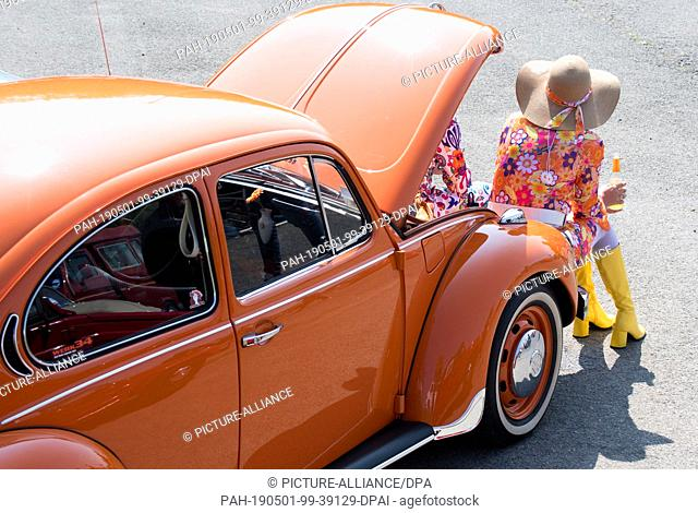 01 May 2019, Lower Saxony, Hanover: Jeanette Nietmann sits at her VW Beetle at the 36th May Beetle Meeting on a parking lot at the fair