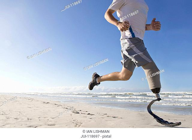 Close Up Of Man With Blade Style Artificial Leg Running On Beach