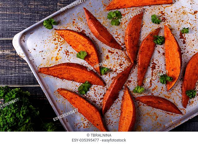 Homemade cooked sweet potatoes with spices and herbs on oven-tray