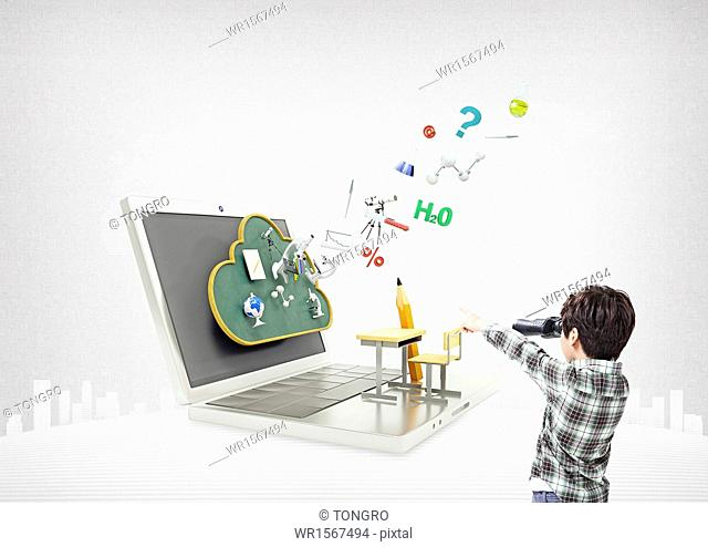 a boy standing in front of a laptop