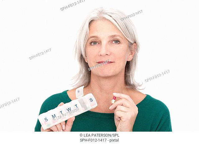 Woman holding pill box and caplet