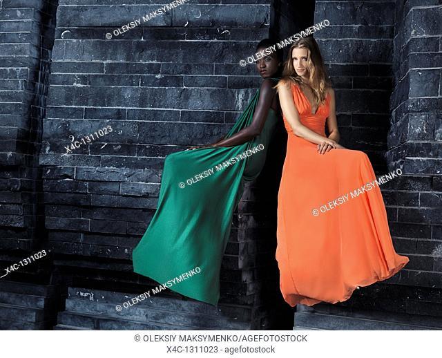 Two beautiful women in elegant dresses sitting on a black stone wall