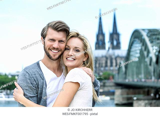 Germany, Cologne, portrait of smiling young couple head to head