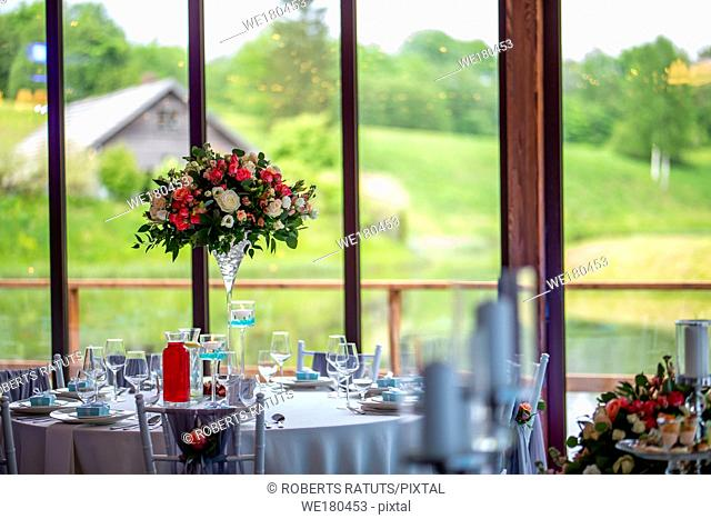 Wedding table decoration. Beautiful bouquet of flowers in vase on the table, next to plates, glasses and gift boxes. Bouquet of flowers, glasses