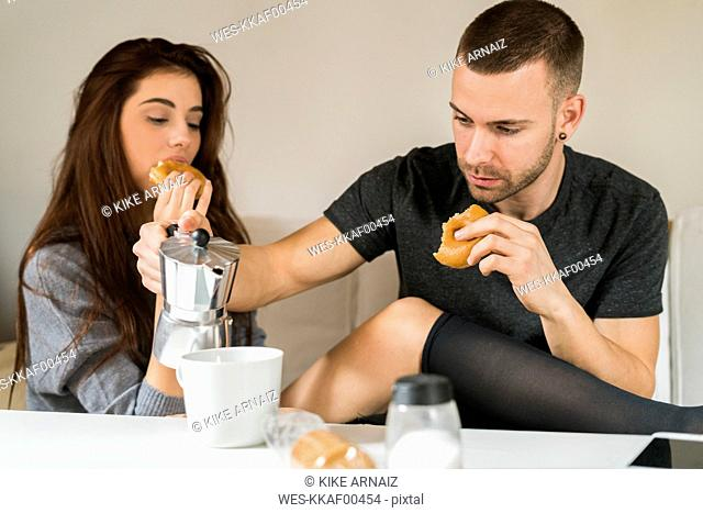 Amorous couple sitting on couch, having breakfast